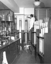 A chemist is shown using column chromatographic apparatus in the mid-1950s to separate constituents in a coal tar color analysis